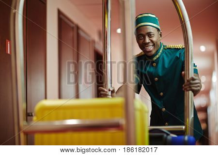 Portrait of smiling African bellhop helping guests, pushing luggage cart delivering bags to hotel rooms