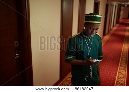 Portrait of African-American bellboy listening to music in hall of hotel, on break from work