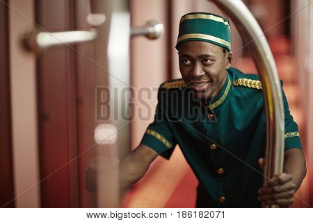 Portrait of cheerful young bellhop helping guests, pushing luggage cart delivering bags to hotel rooms in hallway