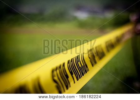 The crime scene murder investigation police surrounded the scene with yellow ribbon that says stop police