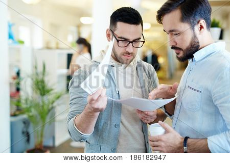 Two bankers reading and discussing papers