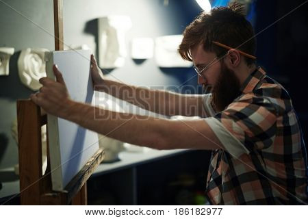 Portrait of modern bearded artist struggling with creativity block looking at blank white canvas trying to think of ideas