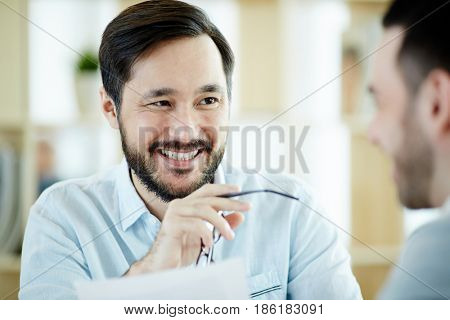 Confident young employer looking at one of applicants during interview
