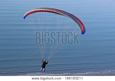 Paraglider flying her wing above the sea