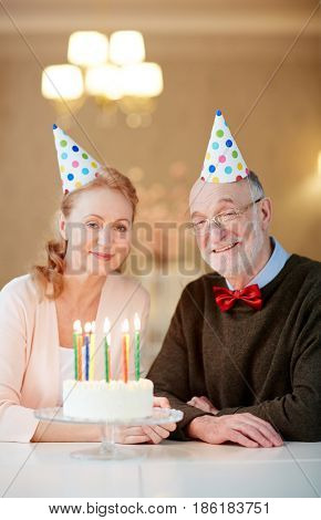 Mature spouses with birthday cake looking at camera