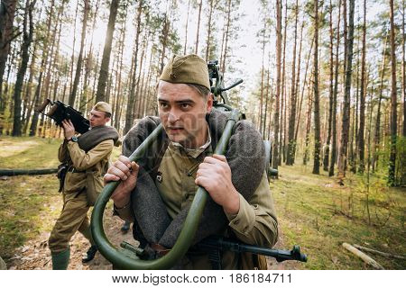Dyatlovichi, Belarus - October 1, 2016: Reenactors Men Dressed As Russian Soviet Red Army Infantry Soldiers Of World War II Marching In Forest With Weapon Machine-gun At Historical Reenactment