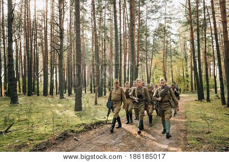 Dyatlovichi, Belarus - October 1, 2016: Group Of Re-enactors Dressed As Soviet Russian Red Army Infantry Soldiers Of World War II Marching Along Forest Road At Autumn Season.