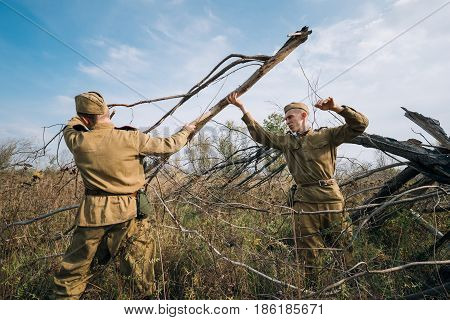 Dyatlovichi, Belarus - October 1, 2016: Two Men Reenactors Dressed As Russian Soviet Red Army Infantry Soldiers Of World War II Equips Camp Prepares Wood For Fire At Historical Reenactment