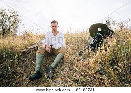 Dyatlovichi, Belarus - October 1, 2016: Reenactor Dressed As Russian Soviet Red Army Soldier Of World War II Sitting Near Maxim Machine Gun Weapon In Ambush In Autumn Meadow At Historical Reenactment