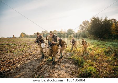 Dyatlovichi, Belarus - October 2, 2016: Group Of Re-enactors Dressed As Russian Soviet Red Army Soldiers Of World War II Running To Enemy Positions Through Autumn Field During Historical Reenactment.