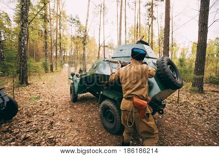 Re-enactor Dressed As Soviet Russian Red Army Infantry Soldier Of World War II Shooting In Attack With Rifle Under Cover Of An Armored Car In Forest At Spring Season.