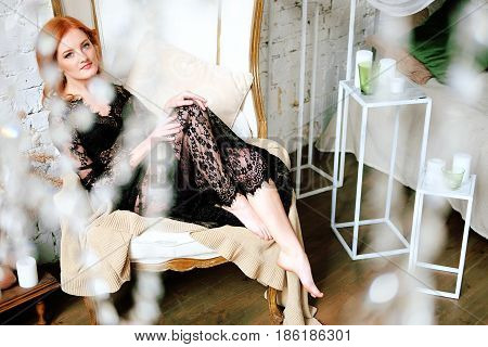 Redhead woman in black lace peignoir sitting in the armchair in her bedroom. Sensual boudoir portrait.