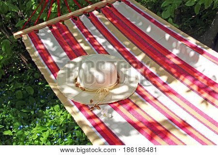 summer: hammock with a lady's sunhat hanging in a garden