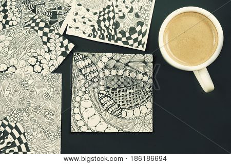 Doodle zen tangle illustration. Zen art doodle patterns for the beginners. Sketch illustrations a pencil and a cup of coffee on the dark wooden table. Lesson for artist painters. Coffee break
