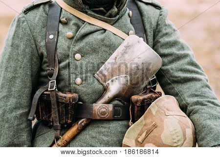 Close up of German military ammunition of a German soldier At World War II. Warm autumn clothes, soldier's overcoat, gloves, helmet, pouch, sapper shovel.