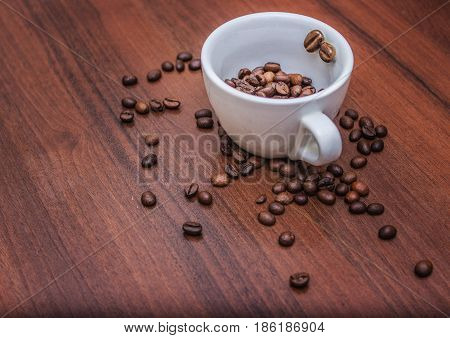 A light cup on a tree filled with coffee beans. Coffee beans in a cup. Coffee on the tree.