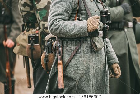 Close up of German military ammunition of a German soldier at World War II. Warm autumn clothes, soldier's overcoat, gloves, helmet, pouch, Sapper shovel, flask, rifle