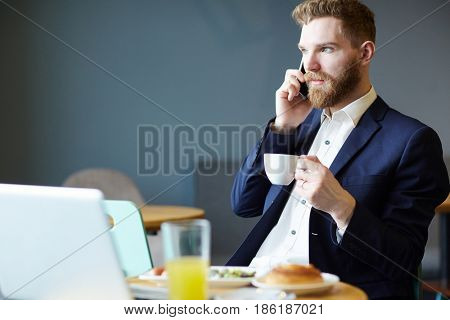 Elegant trader with cup of tea sitting in cafe and talking on smartphone