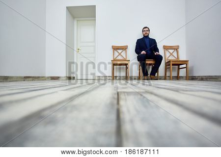 Jobless man sitting on chair and waiting for his turn for interview
