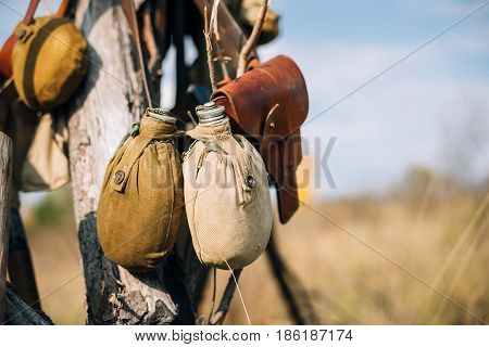 Russian Soviet Red Army Soldier's Military Equipment Of World War II. Flasks And Holster Hanging In Tree Trunk