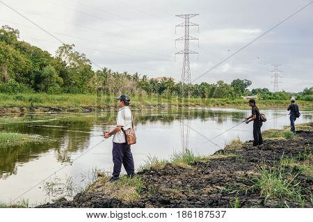 Labuan,Malaysia-May 7,2017:Group of fisherman,fishing with bait casting in the Labuan river,Malaysia.Bait casting is relies on the weight of the lure to extend the line into the target area