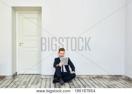Businessman with touchpad sitting on the floor