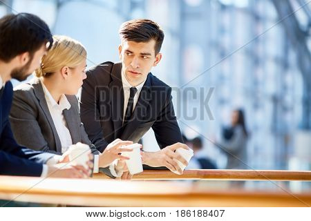 Portrait of three business people, one woman and two men, discussing work at break  in modern office building leaning on railing and holding coffee cups