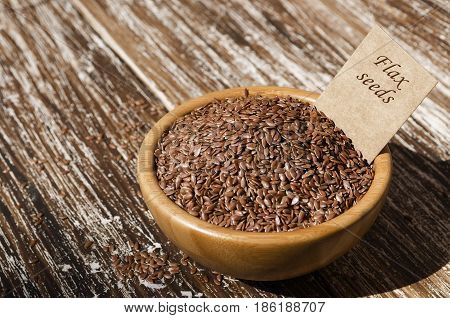 Close up of brown flax seeds in wooden bowl with tag on a rustic table. Superfood: linseeds are high in omega-3 fatty acids essential for good health. Healthy eating vegan diet concept.
