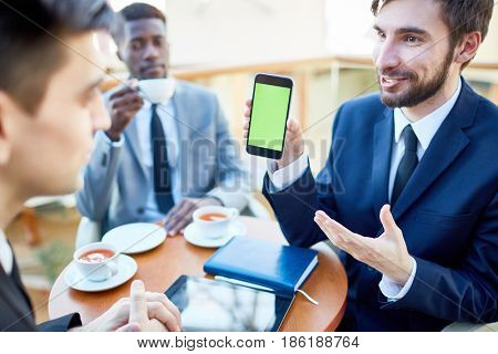 Portrait of modern young businessman enthusiastically presenting mobile app to colleagues showing them smartphone  during meeting in cafe
