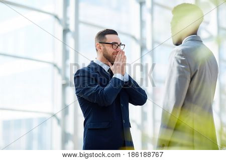 Portrait of successful businesman smiling with happiness while talking to African-American partner standing in modern glass hall of office building
