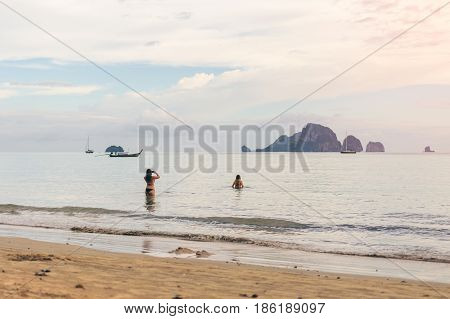Young women traveler with two pieces at the sea take a photo from Ao Nang Beach Krabi. Traveling in Krabi Thailand Traveler summer concept