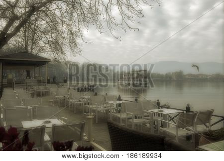 Foggy day on lake Pamvotis. A river barge ship trasfer people to small island into the lake. Ioannina city Greece.Vintage look processed