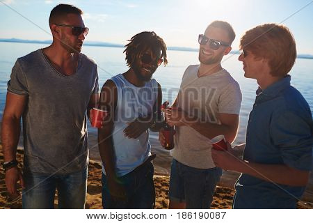 Four buddies with drinks talking on the beach on summer day
