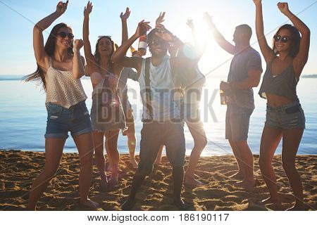 Energetic dance of friendly people on sand