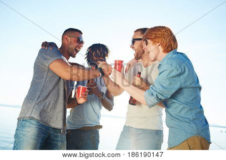 Happy buddies with drinks arm-wrestling on beach
