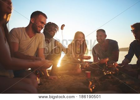 Restful buddies preparing snack on campfire in the evening