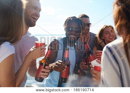 Large group of buddies with drinks spending leisure by seaside