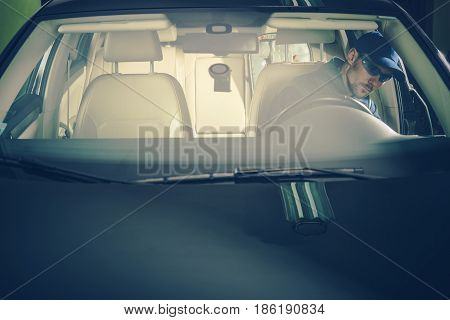 Automotive Engineer Job. Caucasian Auto Service Worker Inside the Vehicle Looking For Issues.