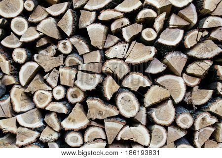 Background of dry chopped oak firewood logs stacked up on top of each other in a pile