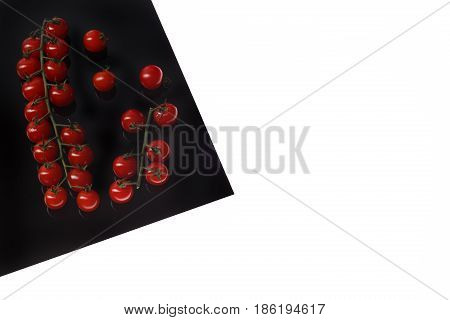 Cherry Tomat on Black Sheet Isolated on white.