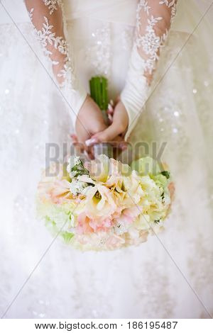 Bride in a beautiful white lacy wedding dress holding a flowers bouquet from white fresh rose in hands. Wedding bridal bouquet close up. Tenderness, love, wedding, fashion - concept.