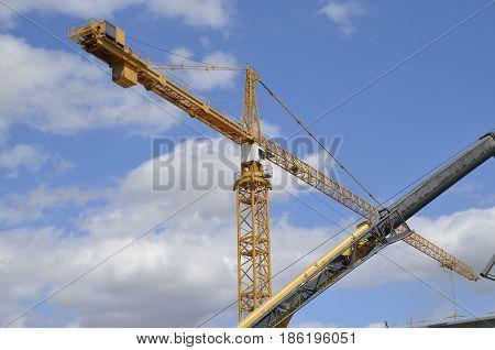 Several huge cranes criss-cross at a construction site