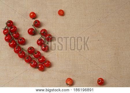 Fresh Cherry tomat lying on a sackcloth surface.