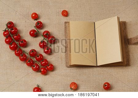 Tomat Cherry and Opened Notebook lying on a sackcloth surface