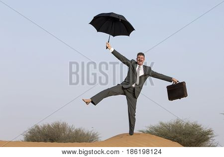 suited buisnessman in a desert with an umbrella