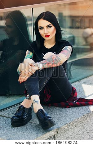 Tattoed Fashion. Portrait Of Beautiful Young Tattoed Hipster Girl Posing To Camera While Sitting Aga