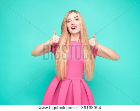 The beautiful young woman in pink mini dress posing at the studio on blue background with sign Ok.