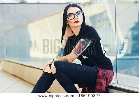 Gothic Beauty. Portrait Of Attractive Tattoed Hipster Girl In Glasses Posing To Camera While Sitting