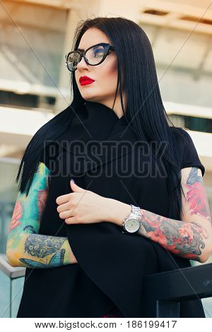 Gothic Beauty. Portrait Of Attractive Tattoed Hipster Girl With Red Lips Posing To Camera While Stan