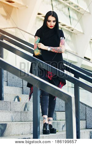 Urban Gothic Woman. Full-length Shot Of Attractive Tattoed Hipster Girl Standing Against Urban Backg